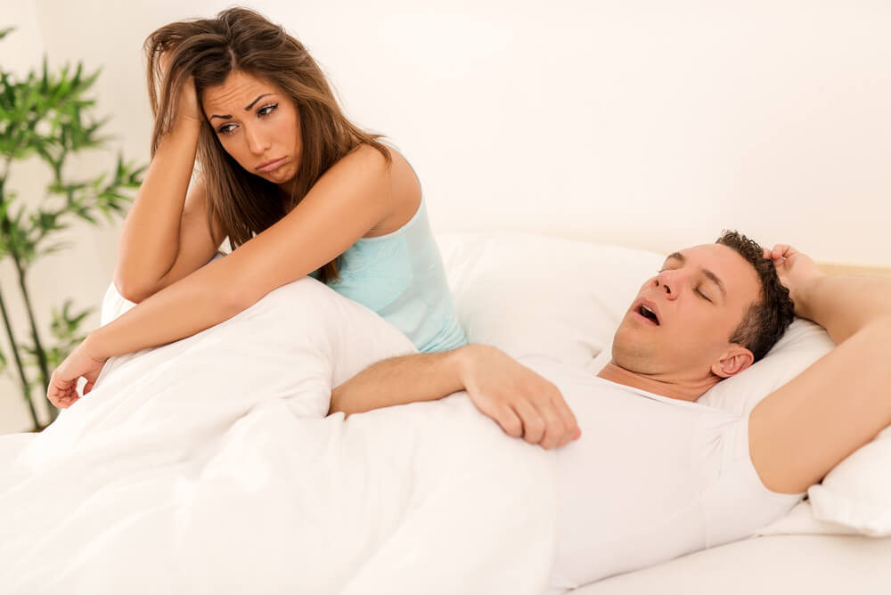 couple in bed, man snoring, woman can't sleep