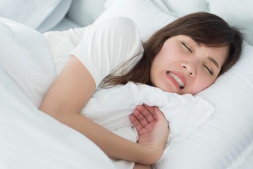 woman grinding her teeth in her sleep due to bruxism