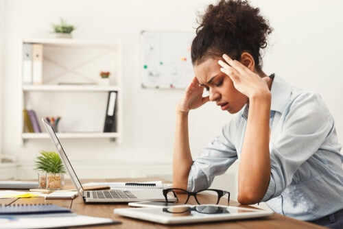 woman at her desk with headache from bruxism