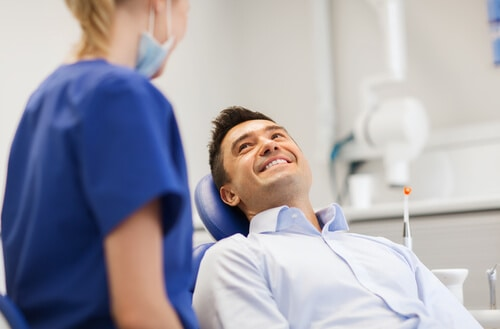 smiling man in dentist chair with dentist
