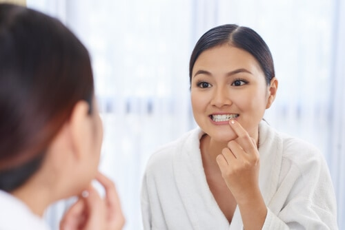 woman looking at white straight teeth in mirror