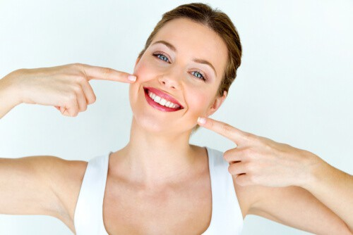 woman with white teeth smiling and pointing to mouth