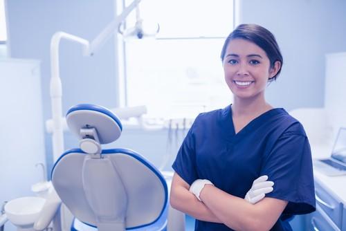 smiling female dentist stood in dental practice in wembley