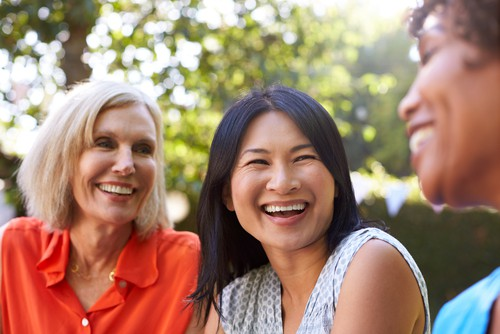 group of three older female friends smiling with confidence - cosmetic dentistry wembley